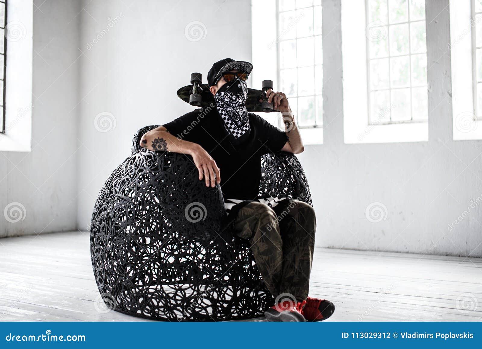 Hombre en máscara del gángster con el monopatín
