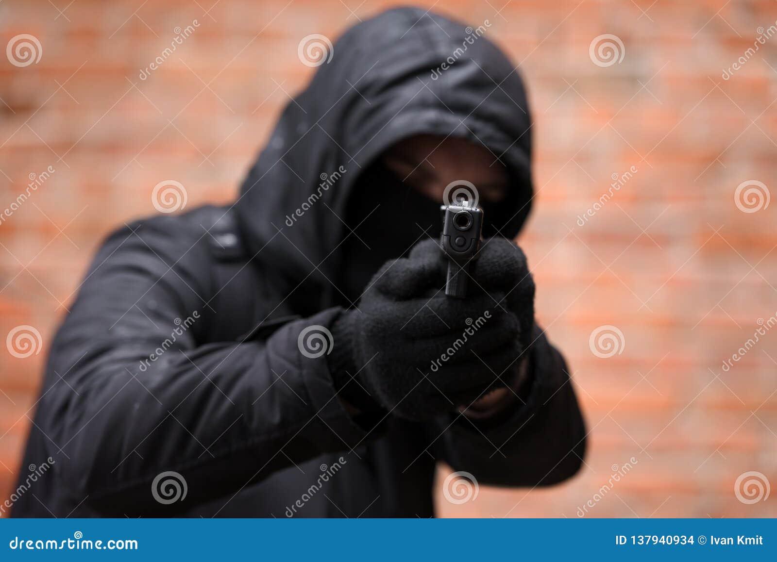 Hombre en máscara negra con la arma de mano