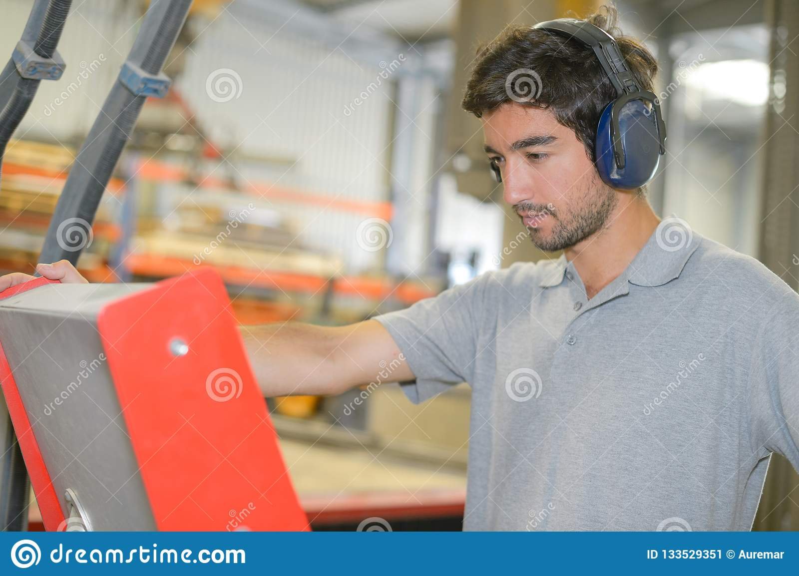 Hombre en protectores contra el ruido de la fábrica que llevan