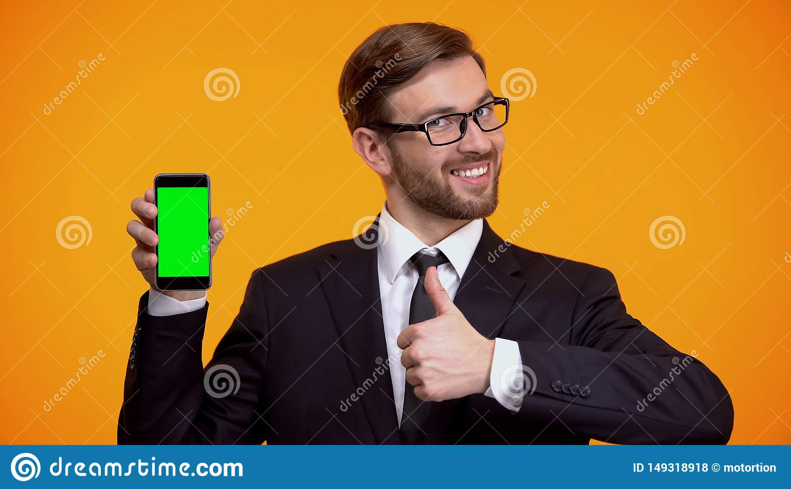 Hombre en smartphone de la tenencia del traje con la pantalla verde, mostrando los pulgares encima del app del negocio