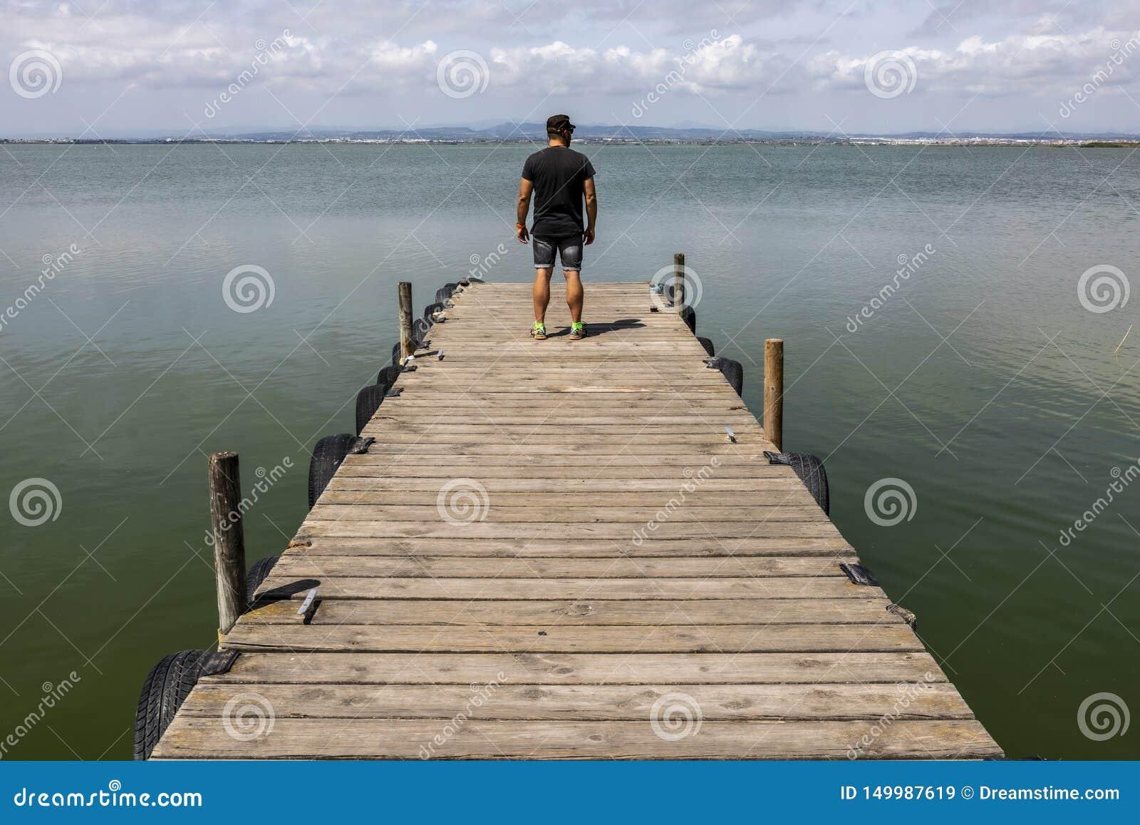 Hombre en un muelle por el lago en el cielo de la mañana