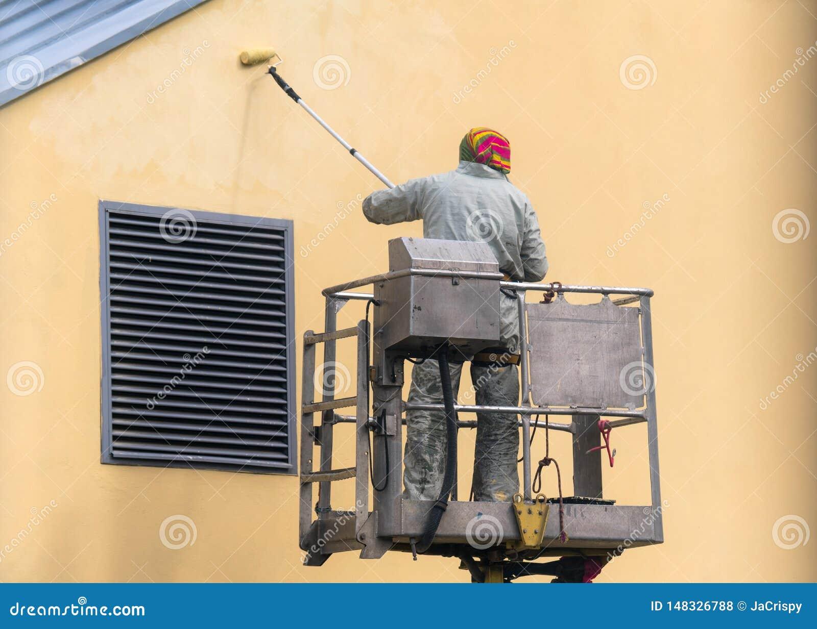 Hombre en una plataforma de elevaci?n que pinta la pared constructiva con un aire libre exterior del rodillo Trabajador en una es