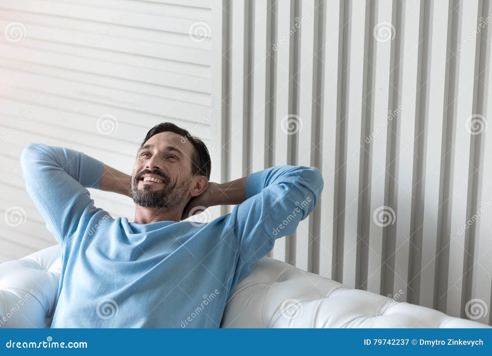 Hombre encantado feliz que lleva a cabo sus manos detrás de la cabeza