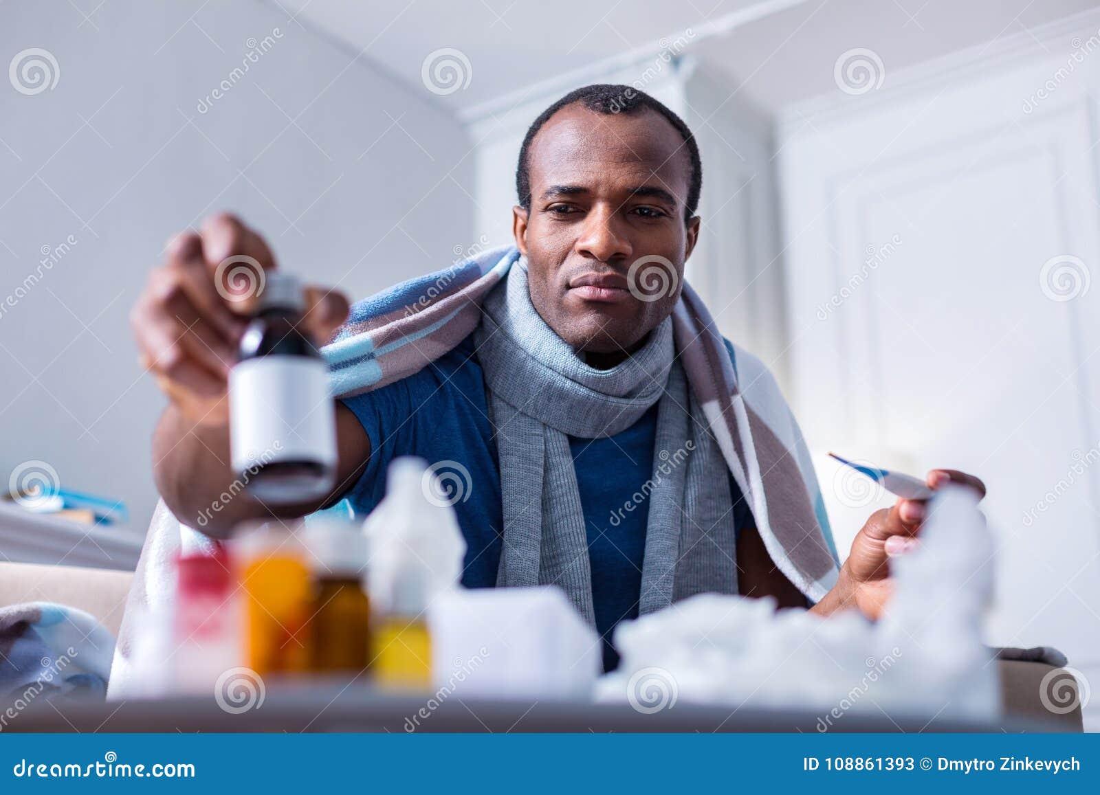 Hombre enfermo serio que toma una botella con la medicina