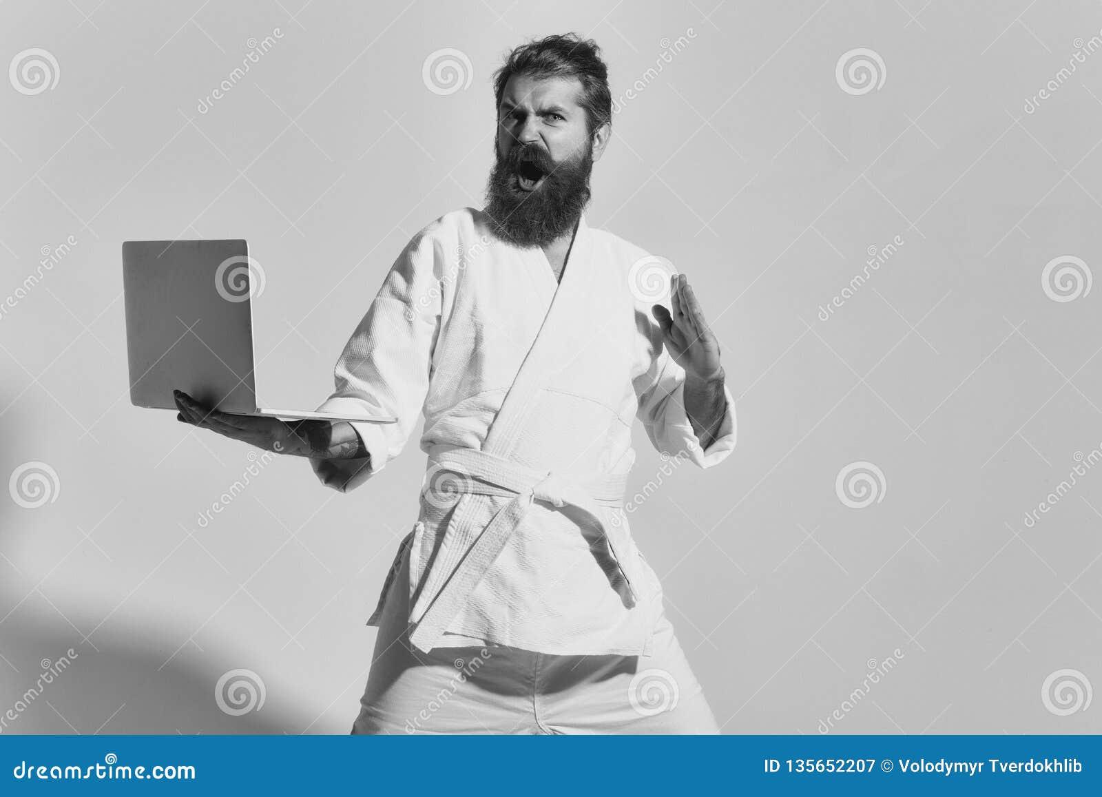 Hombre enojado barbudo del karate en kimono con el ordenador portátil