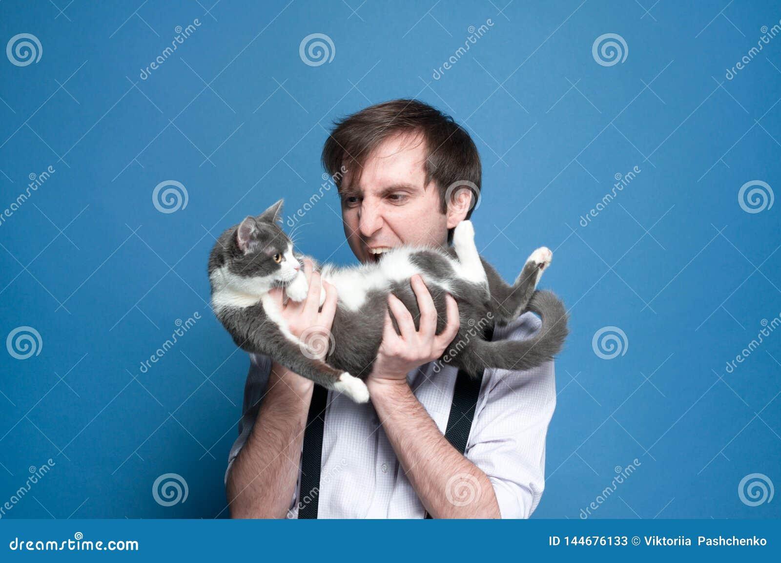 Hombre enojado con la boca abierta que se sostiene y que mira al gato gris y blanco lindo