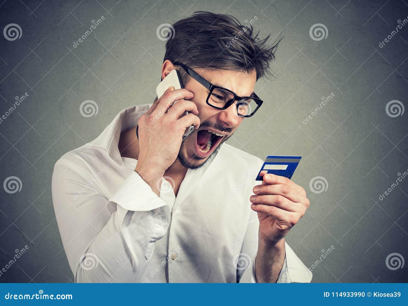Hombre enojado de griterío que soluciona problemas con la tarjeta de crédito