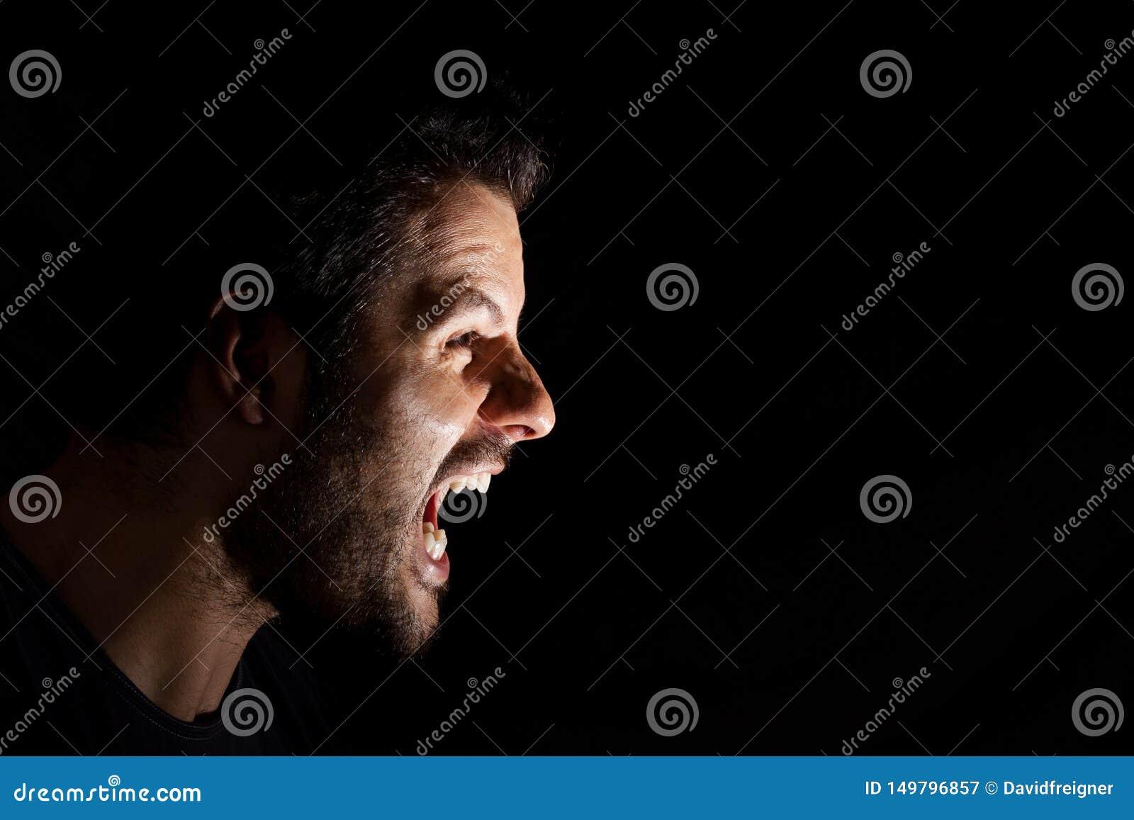 Hombre enojado que grita hacia fuera aislado ruidosamente en fondo negro