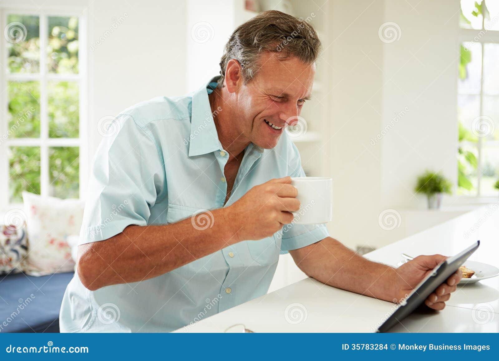 Hombre envejecido centro que usa la tableta de Digitaces sobre el desayuno