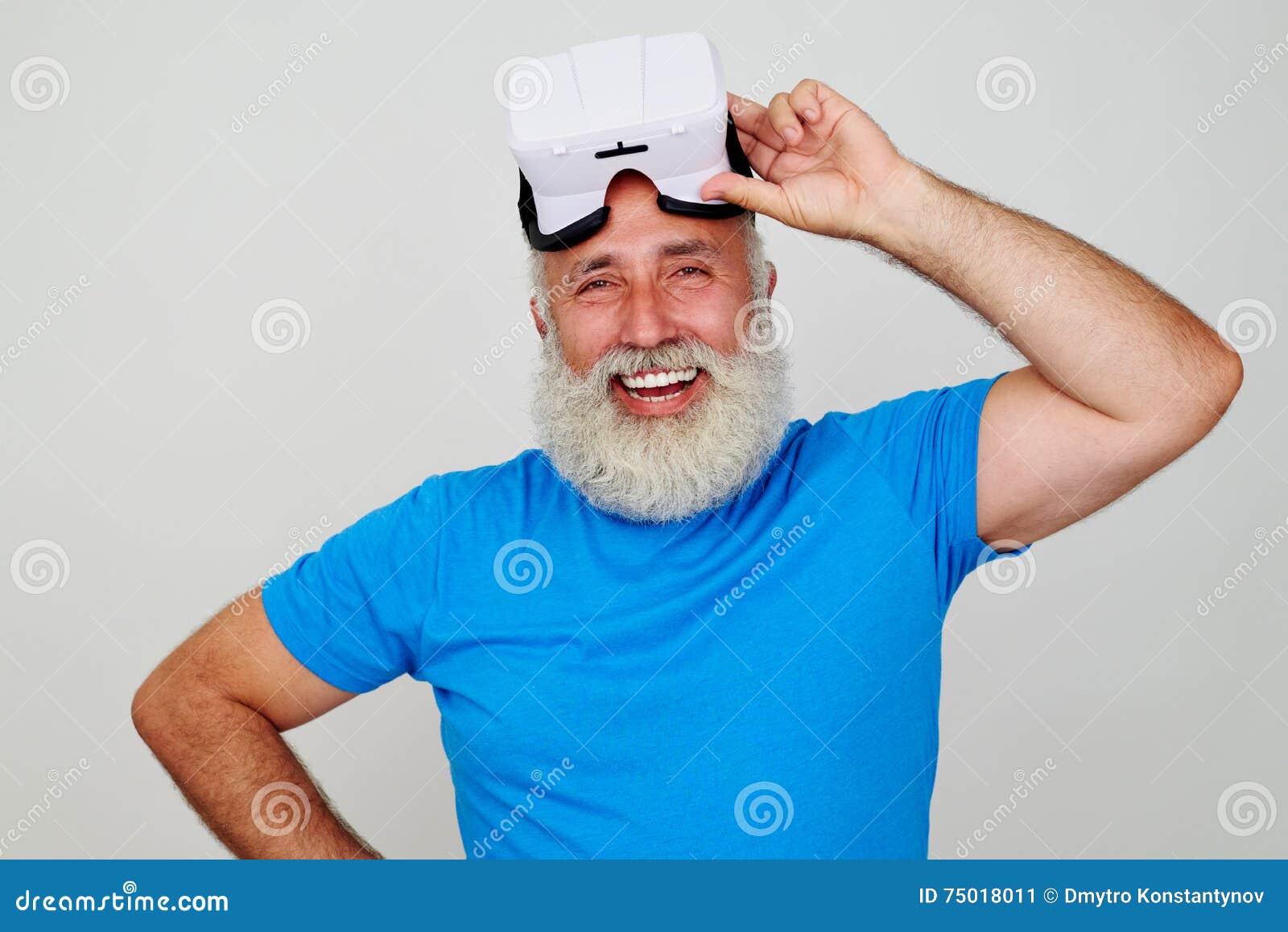 Hombre envejecido sonriente satisfecho por el trabajo de las auriculares de la realidad virtual