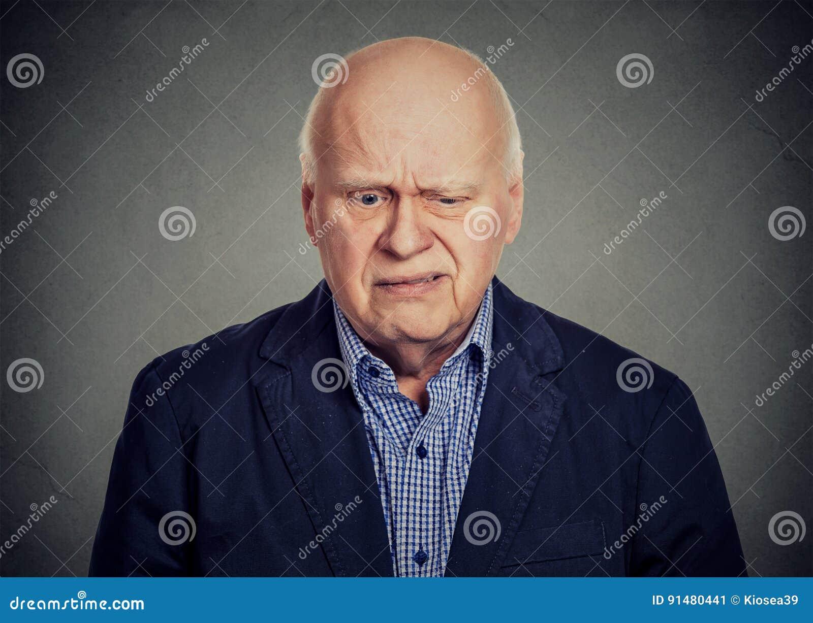Hombre escéptico triste mayor que mira abajo