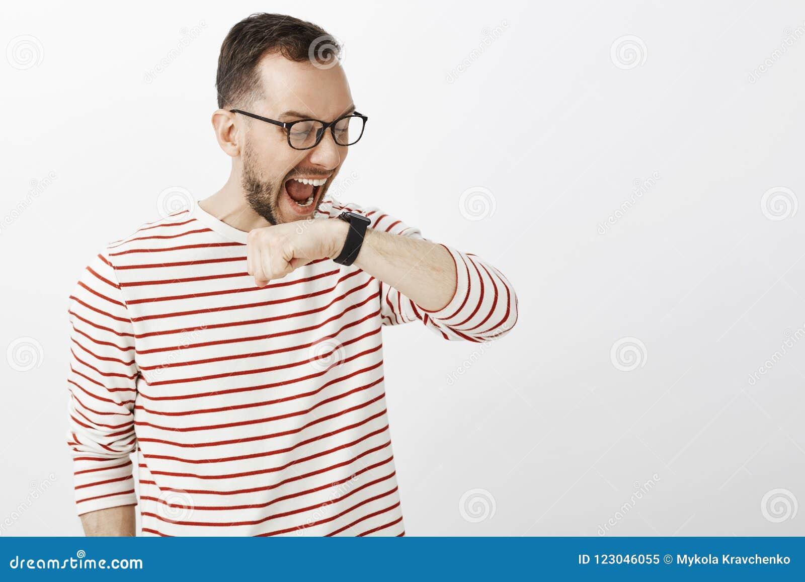 Hombre europeo gritador divertido en vidrios, aumentando el brazo cerca de cara y gritando en el reloj digital negro, haciendo co