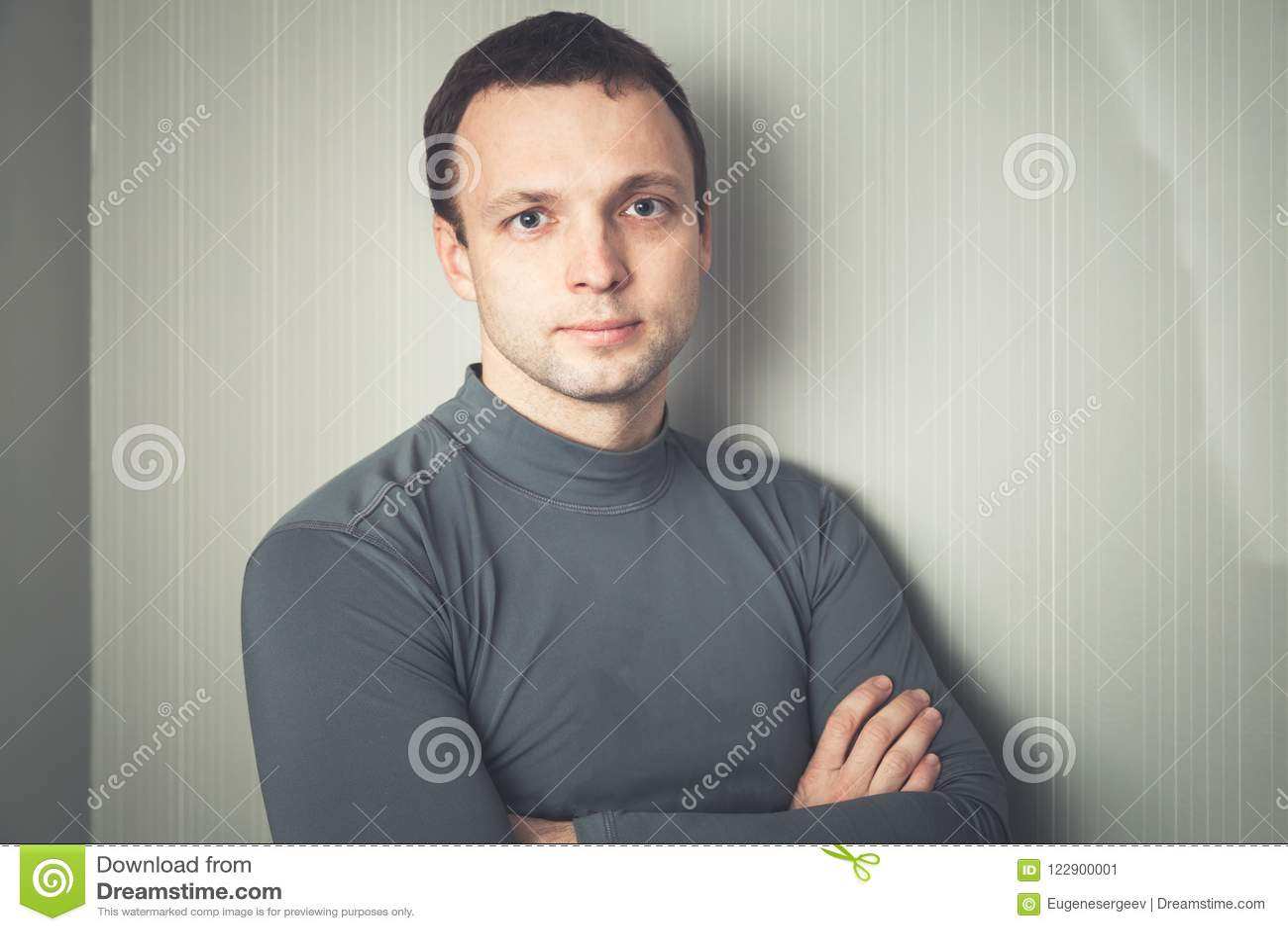 Hombre europeo serio en ropa de deportes gris