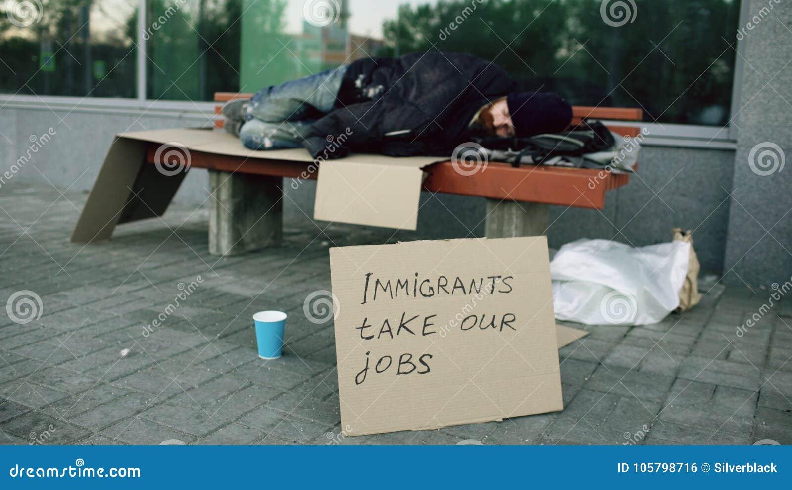 Hombre europeo sin hogar y desempleado con sueño de la muestra de la cartulina en banco en la calle de la ciudad debido a crisis