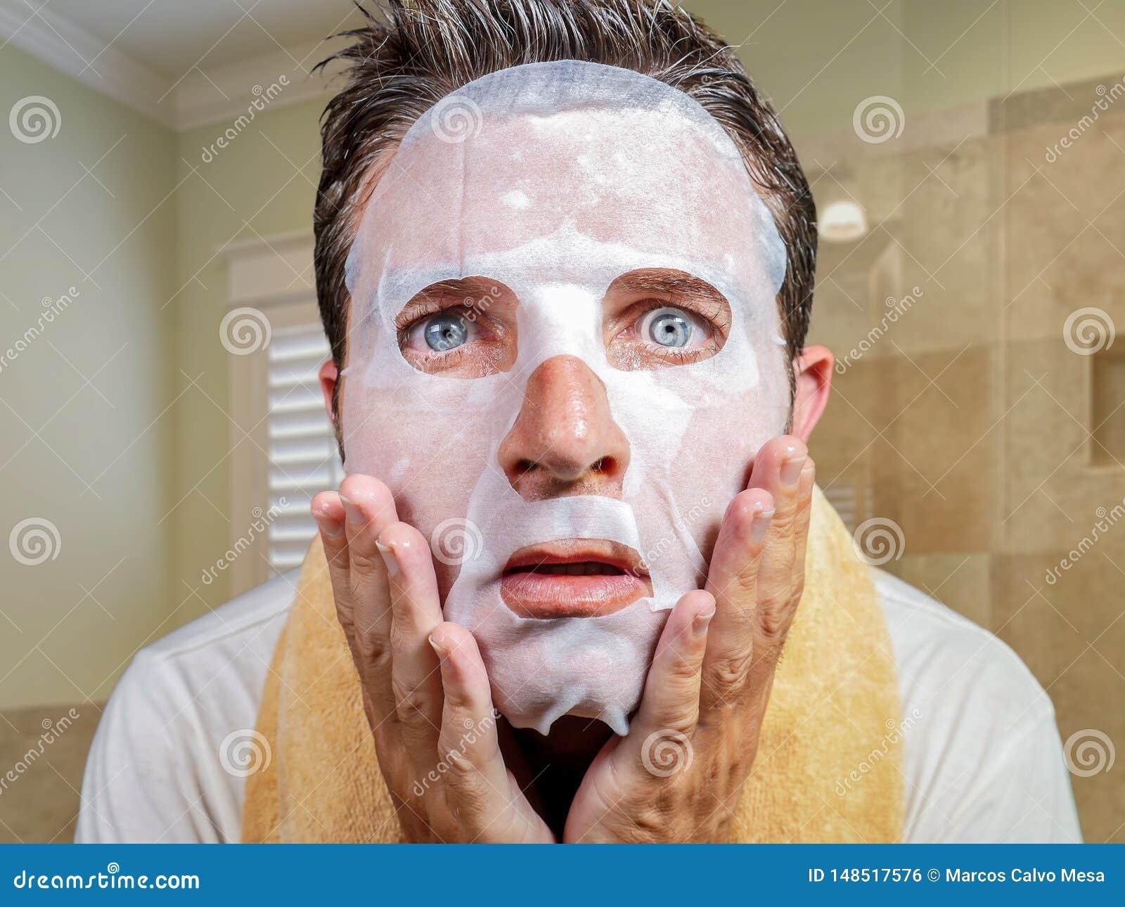 Hombre extra?o y divertido joven en casa que intenta usando la m?scara facial del papel de la belleza que limpia aprendiendo el t