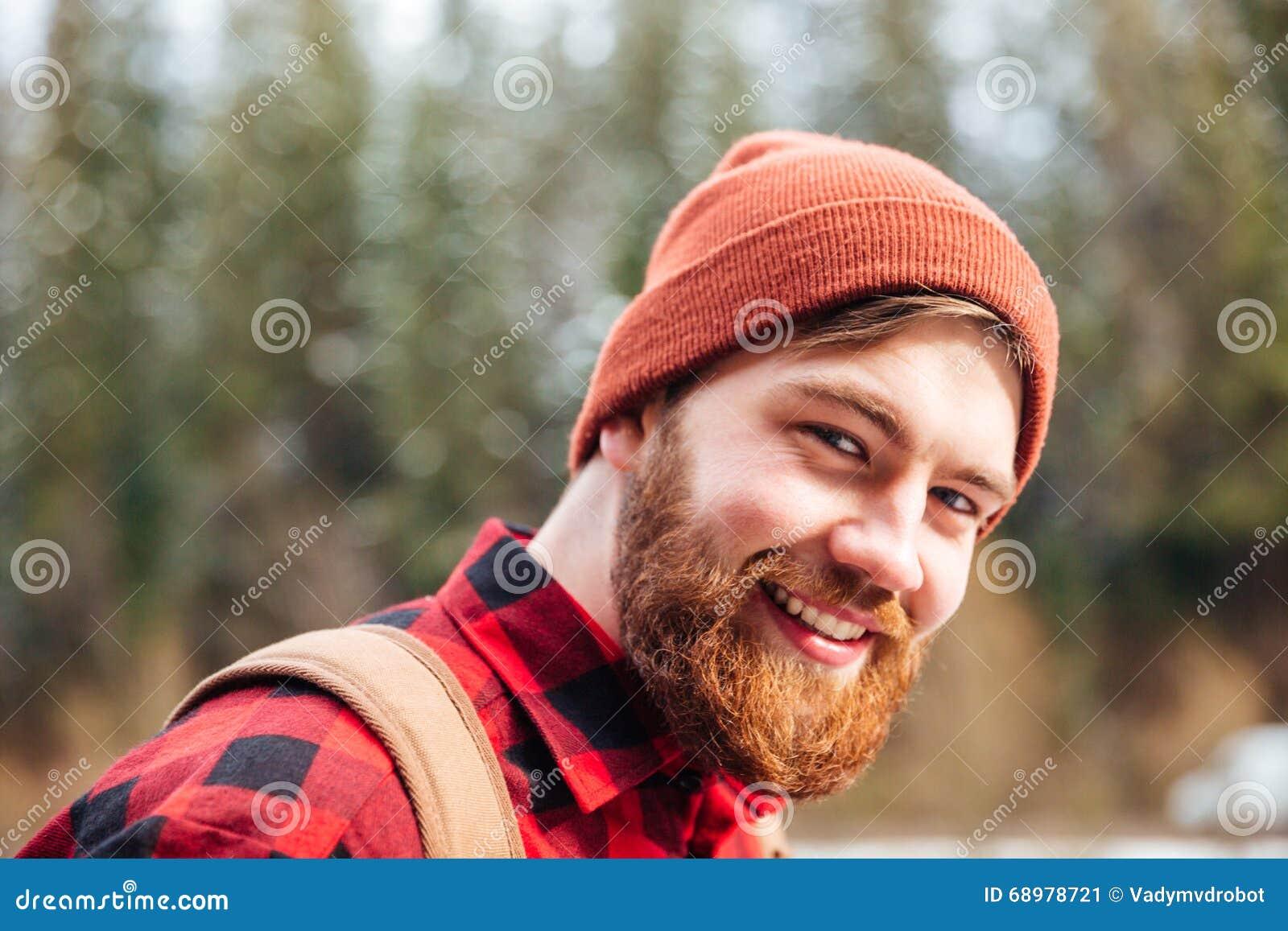Hombre feliz con la barba en sombrero y camisa a cuadros al aire libre