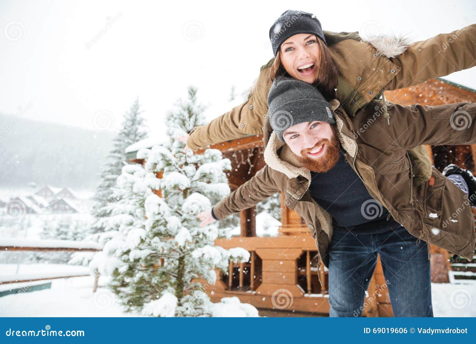 Hombre feliz piggibacking su novia y que ríe en invierno