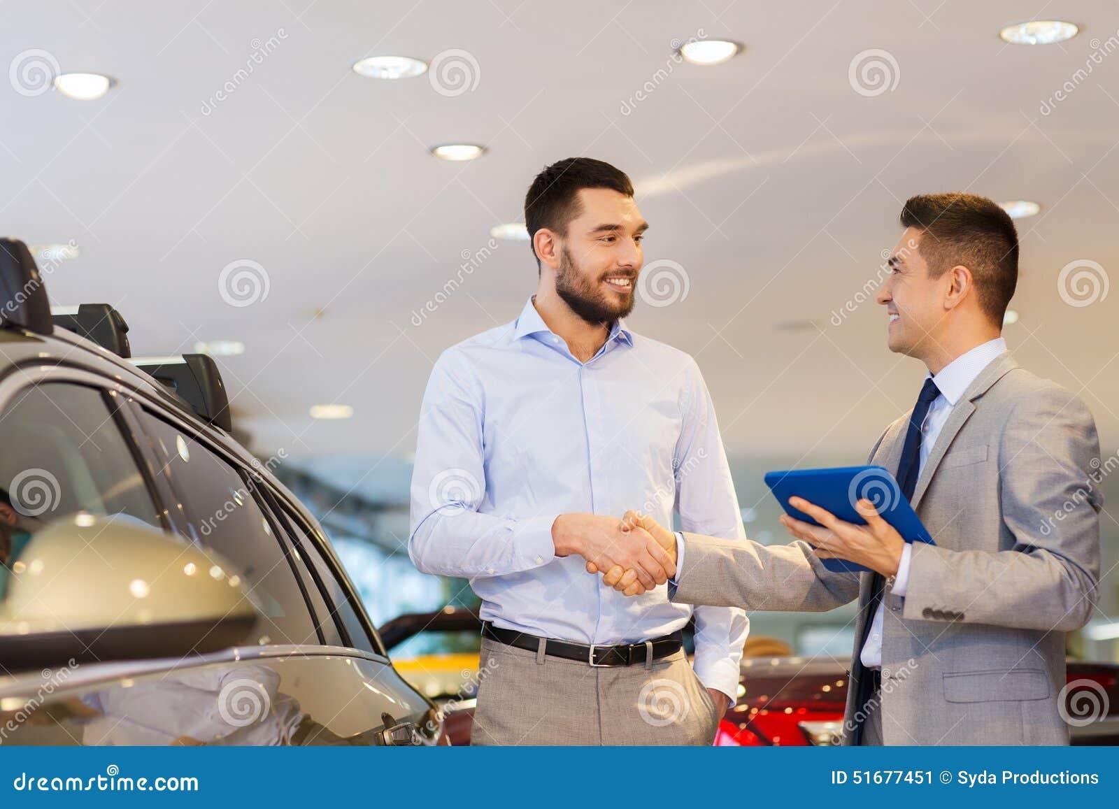 Hombre feliz que sacude las manos en salón del automóvil o salón
