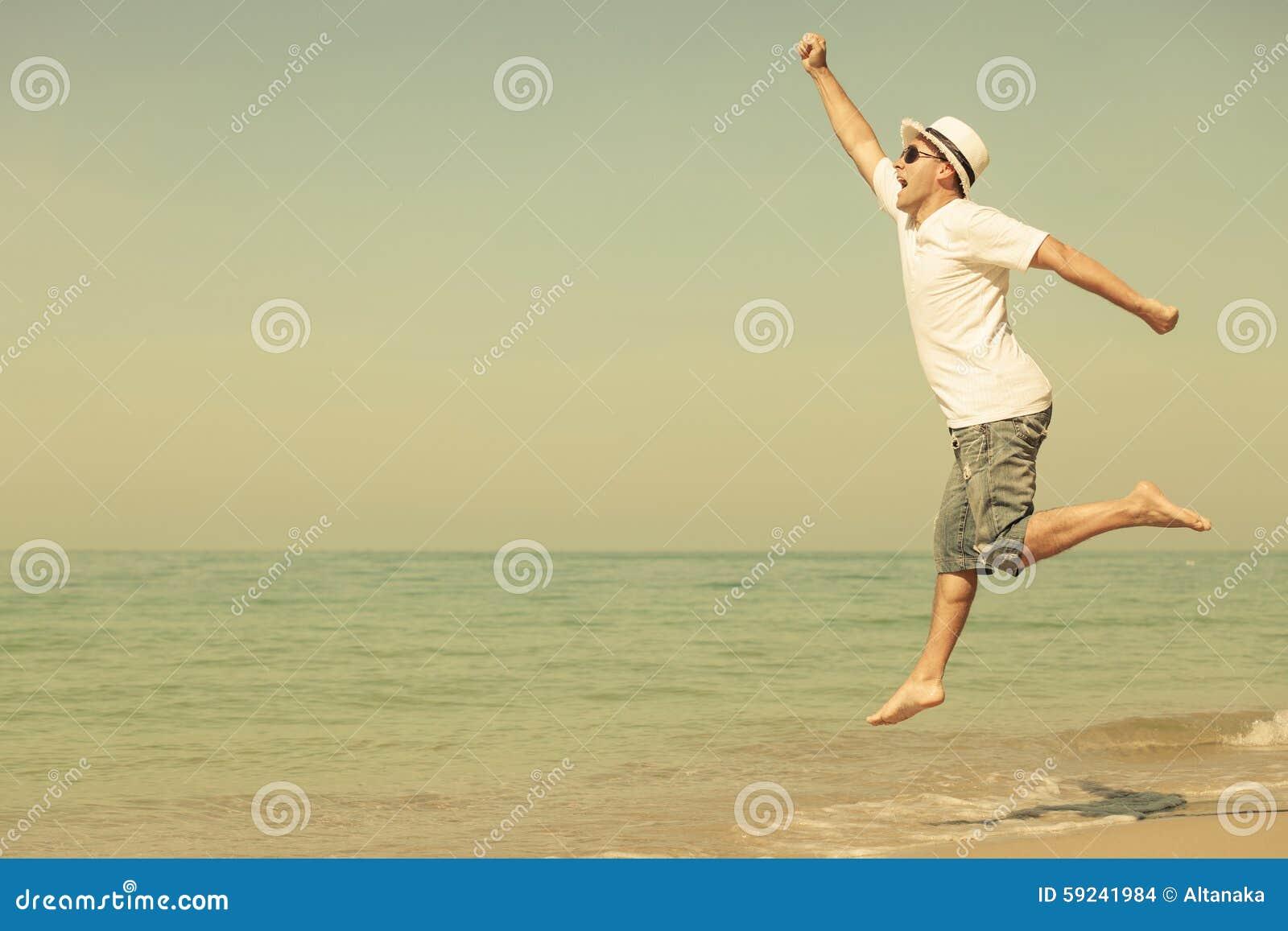 Hombre feliz que salta en la playa