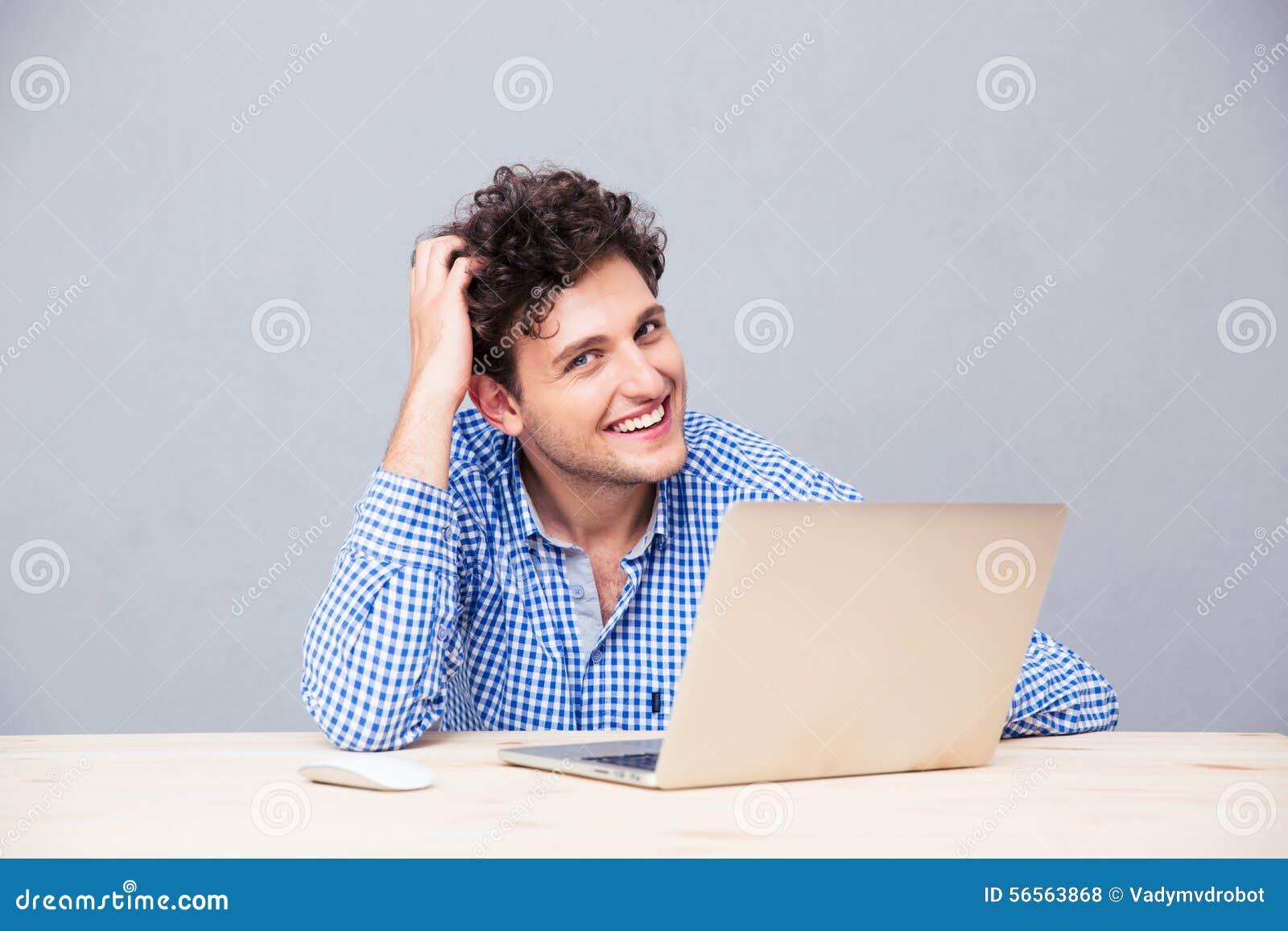 Hombre feliz que se sienta en la tabla con el ordenador portátil