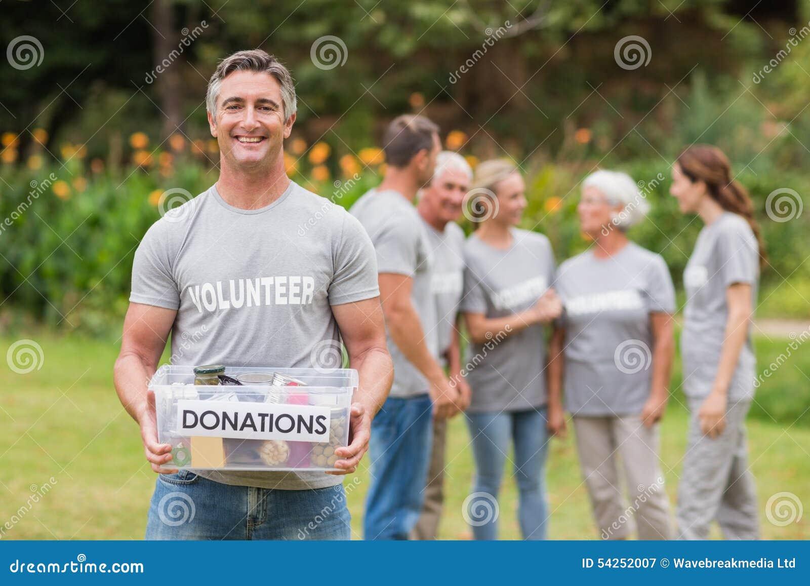 Hombre feliz que sostiene las cajas de las donaciones