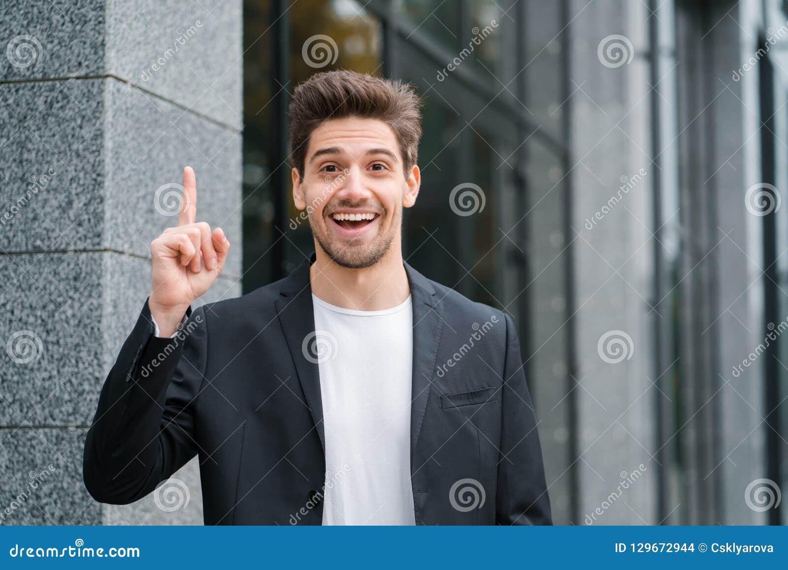 Hombre feliz sonriente del estudiante que muestra el gesto de Eureka Retrato del hombre de negocios de reflexión de pensamiento j