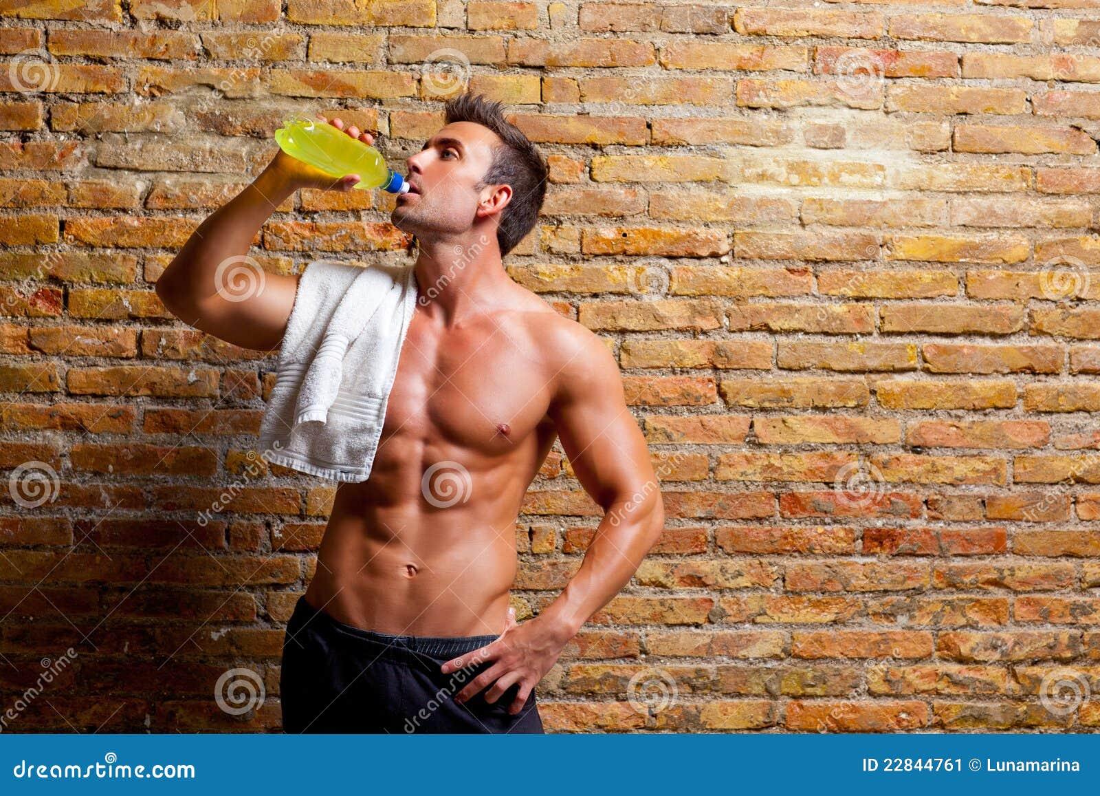Hombre formado músculo en la consumición relajada gimnasia