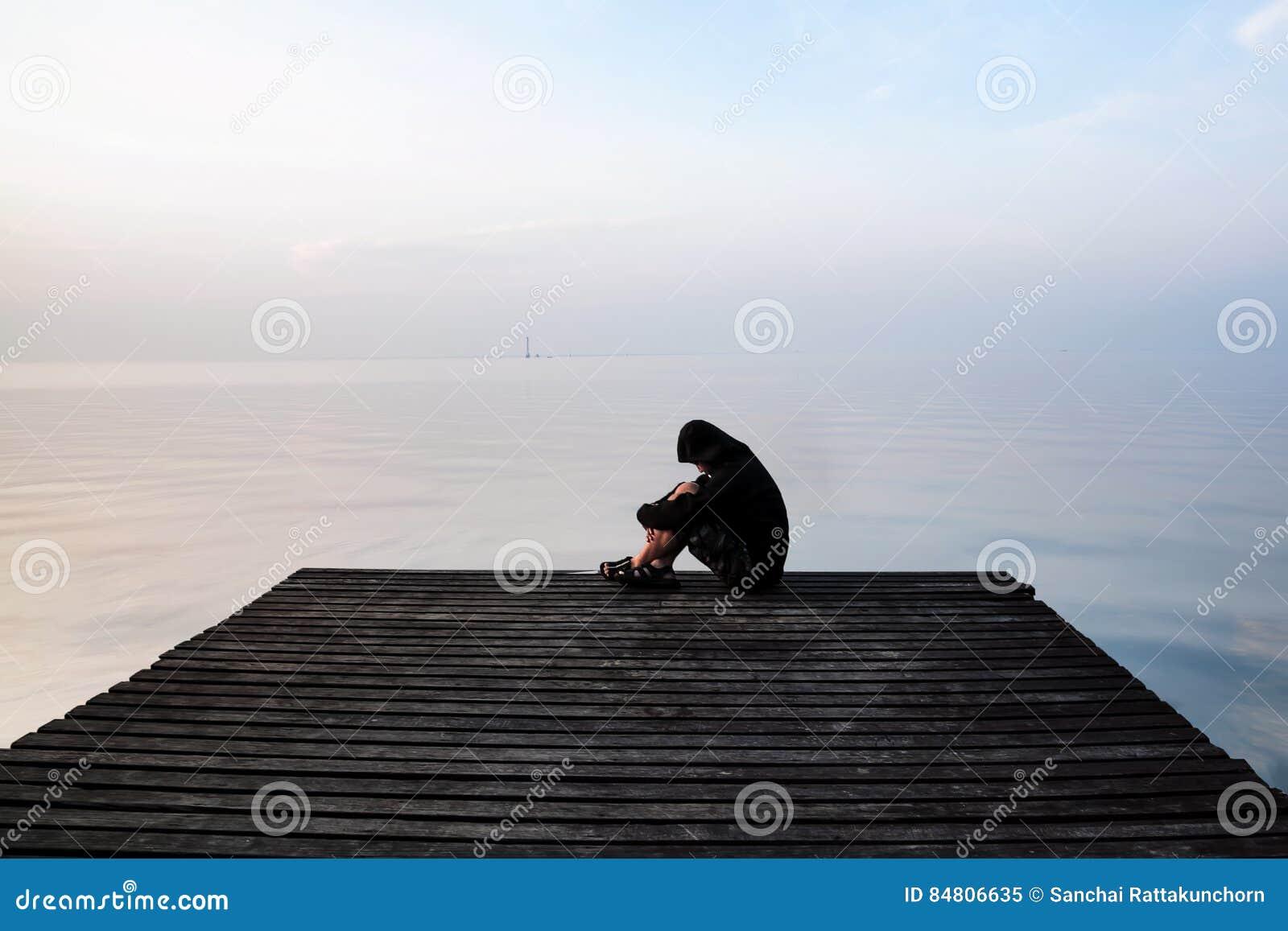 Hombre frustrado de la depresión en la capilla que se sienta en el puente de madera,