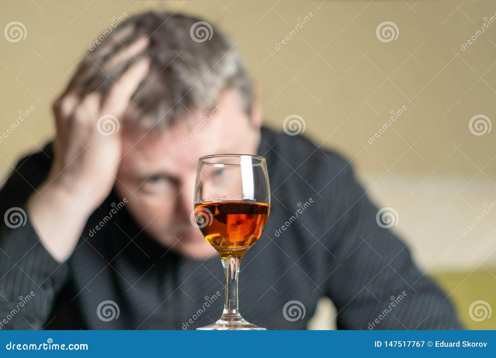 Hombre fuera de miradas del foco en un vidrio de brandy