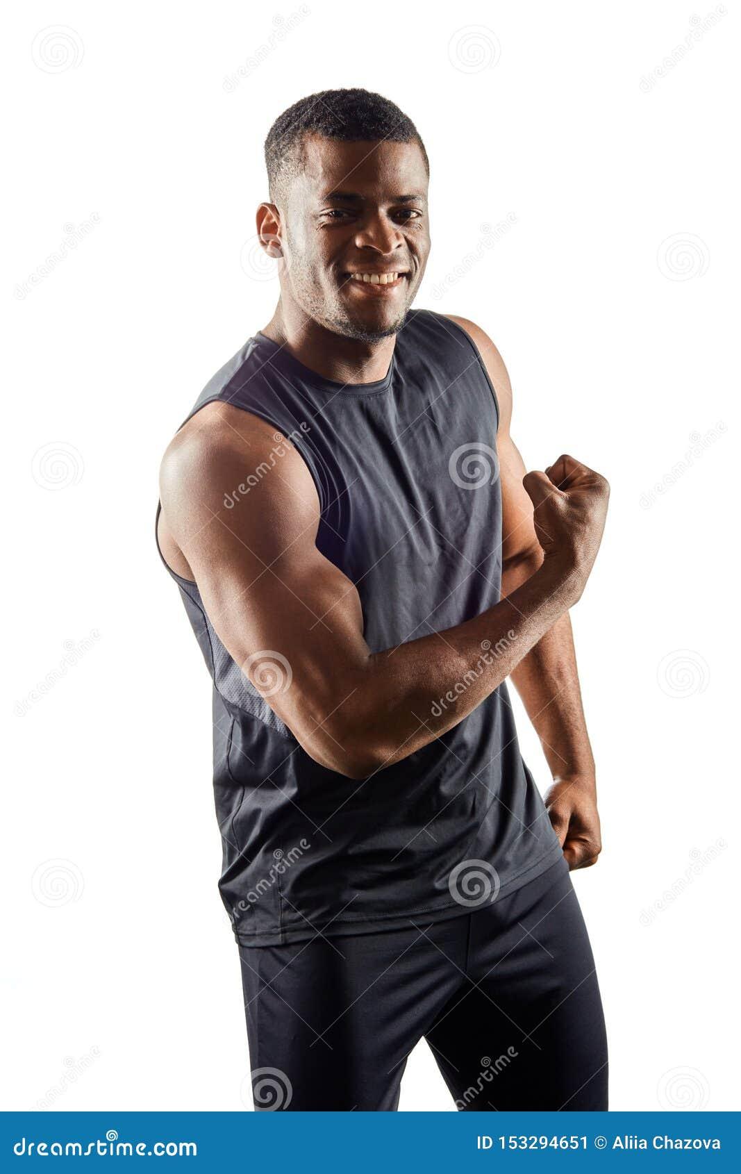 Hombre fuerte feliz alegre africano que muestra sus músculos