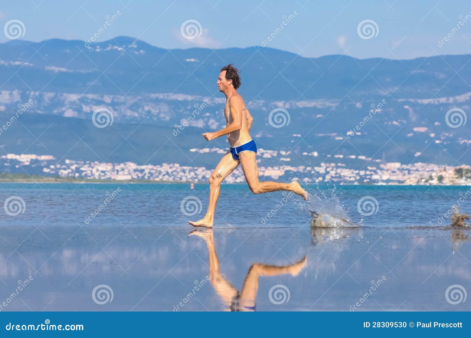 Hombre funcionado con a través de la playa