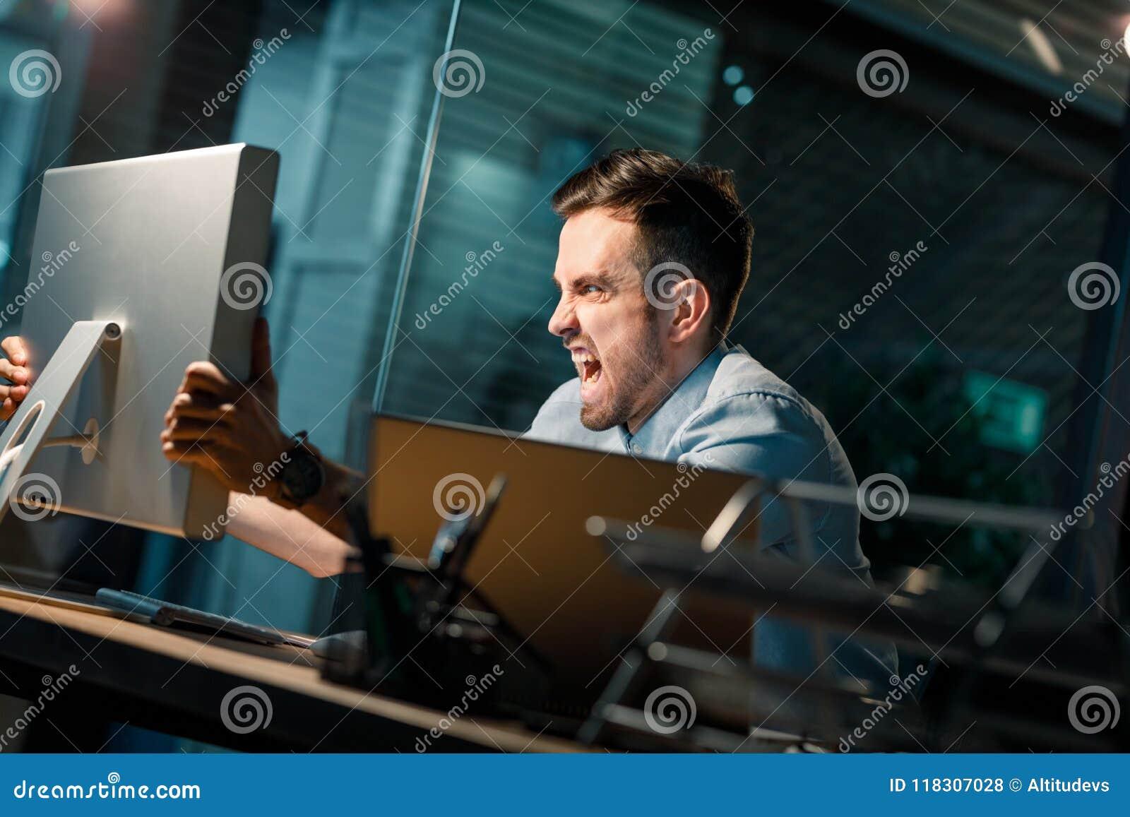 Hombre furioso que grita en el ordenador