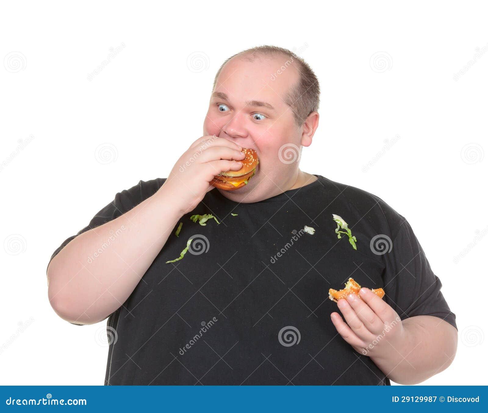 Hombre gordo codicioso que come la hamburguesa