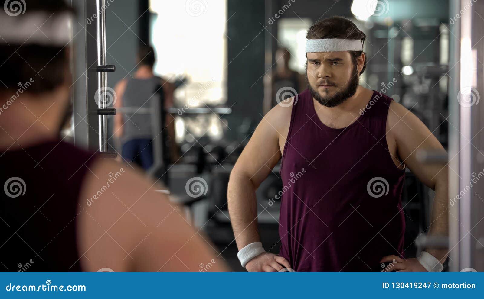 Hombre gordo infeliz que mira su reflexión de espejo en gimnasio, dieta y deporte