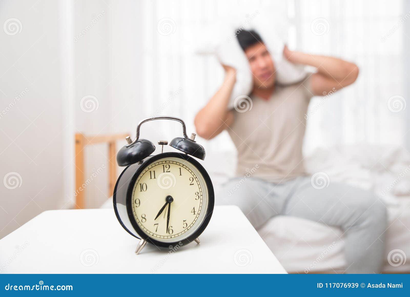 Hombre hermoso asiático despertado por el despertador en la cama en el tiempo de mañana