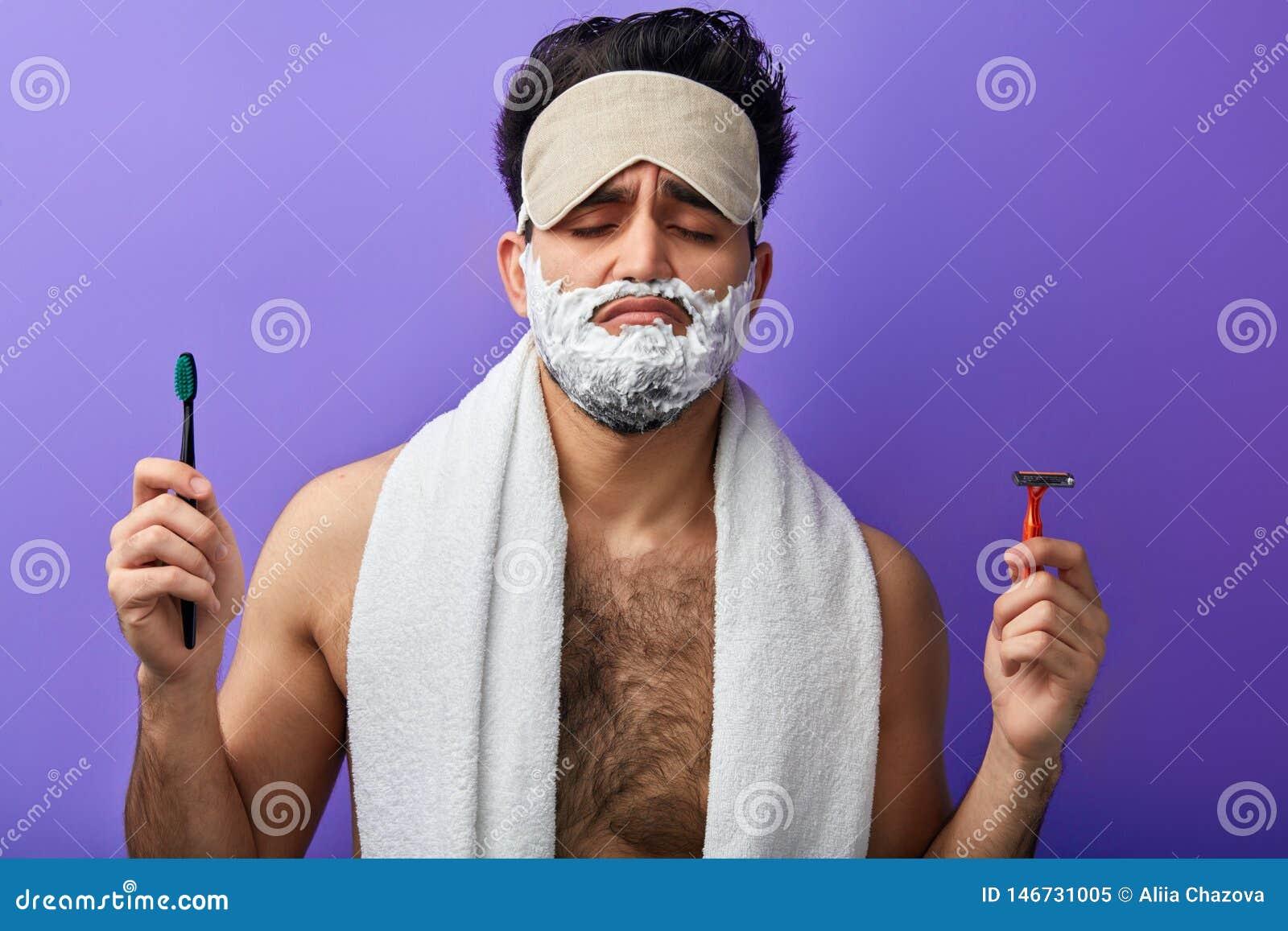 Hombre hermoso atractivo soñoliento con los ojos cerrados, afeitando espuma en su cara