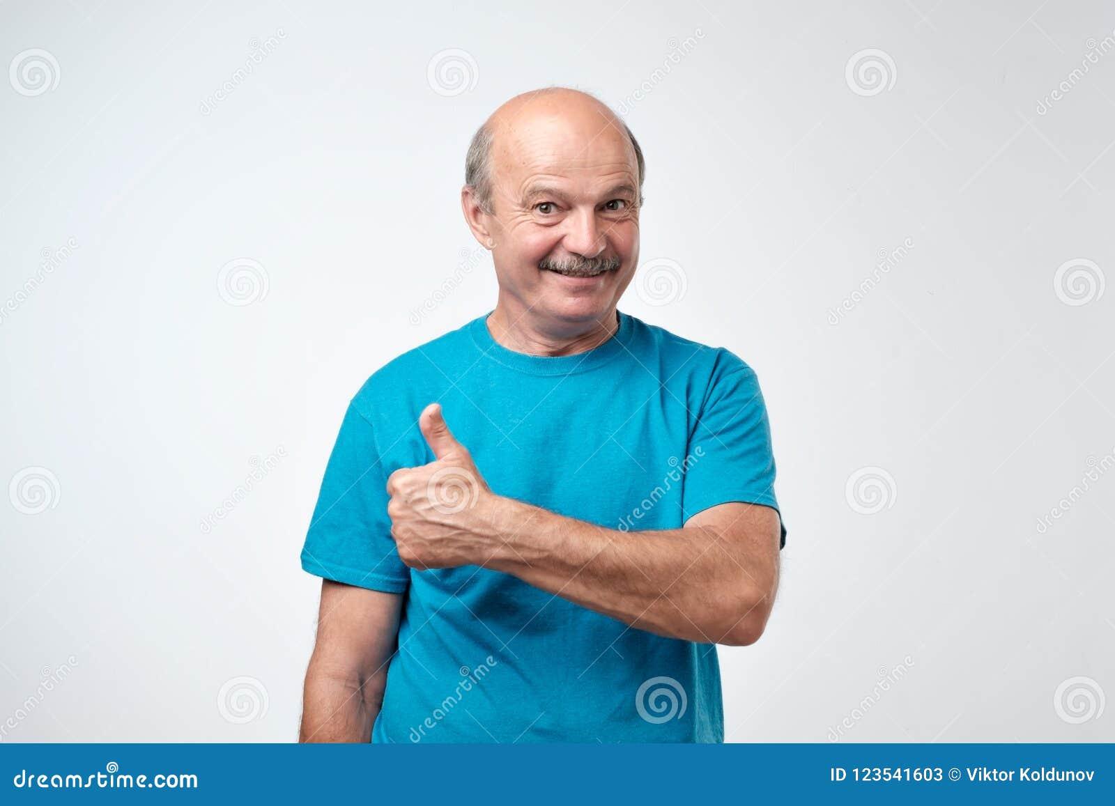 Hombre hermoso, calvo con su pulgar para arriba en la muestra del optimismo en el fondo blanco