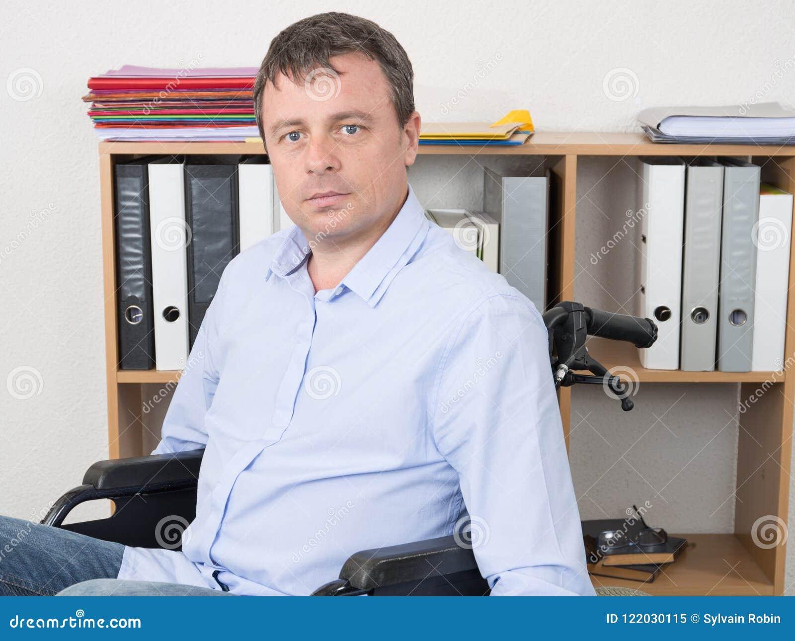Hombre hermoso en oficina de la silla de ruedas en casa