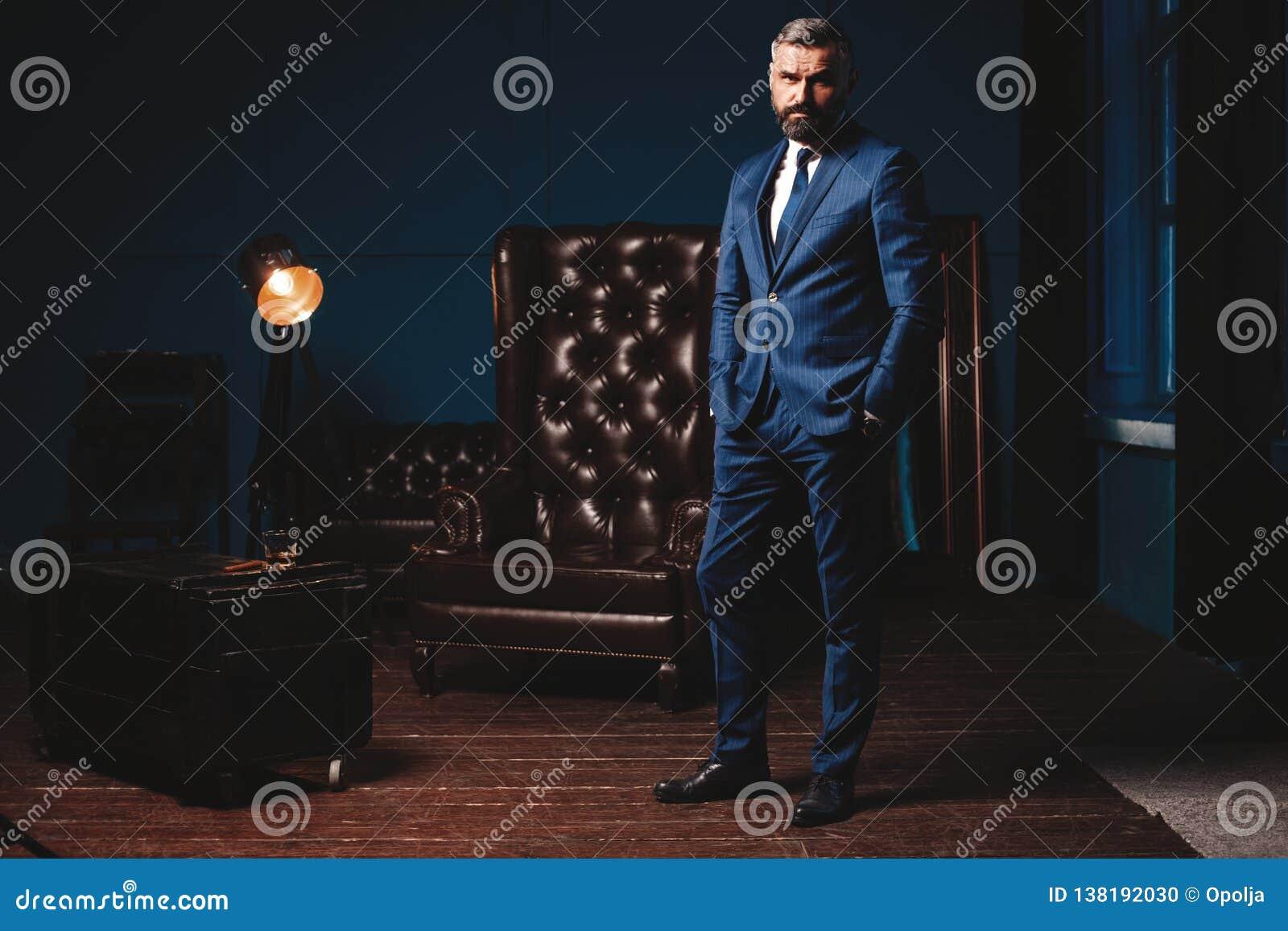 Hombre hermoso en traje elegante en interior de lujo Retrato del primer del hombre confiado de moda en el apartamento lujoso