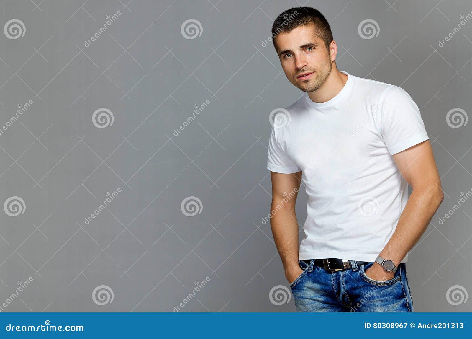 c8e134c67 Hombre Hermoso En Una Camiseta Blanca Y Vaqueros Imagen de archivo ...
