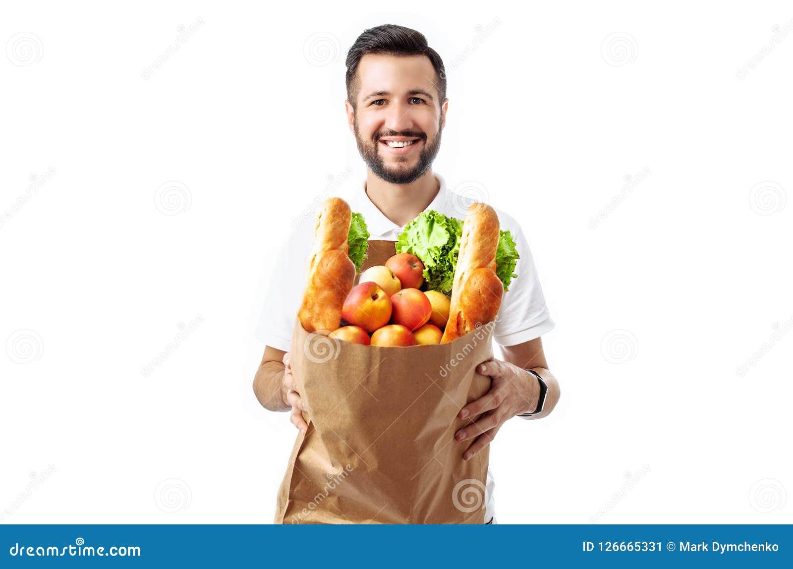 Hombre hermoso joven del inconformista que sostiene un bolso de la comida aislado en un fondo blanco