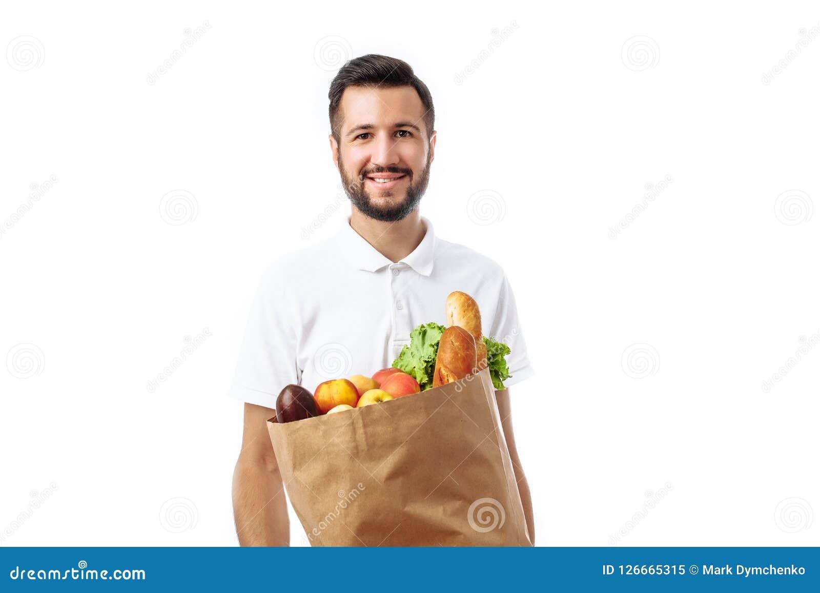 Hombre hermoso joven del inconformista que sostiene un bolso de la comida aislado en un w