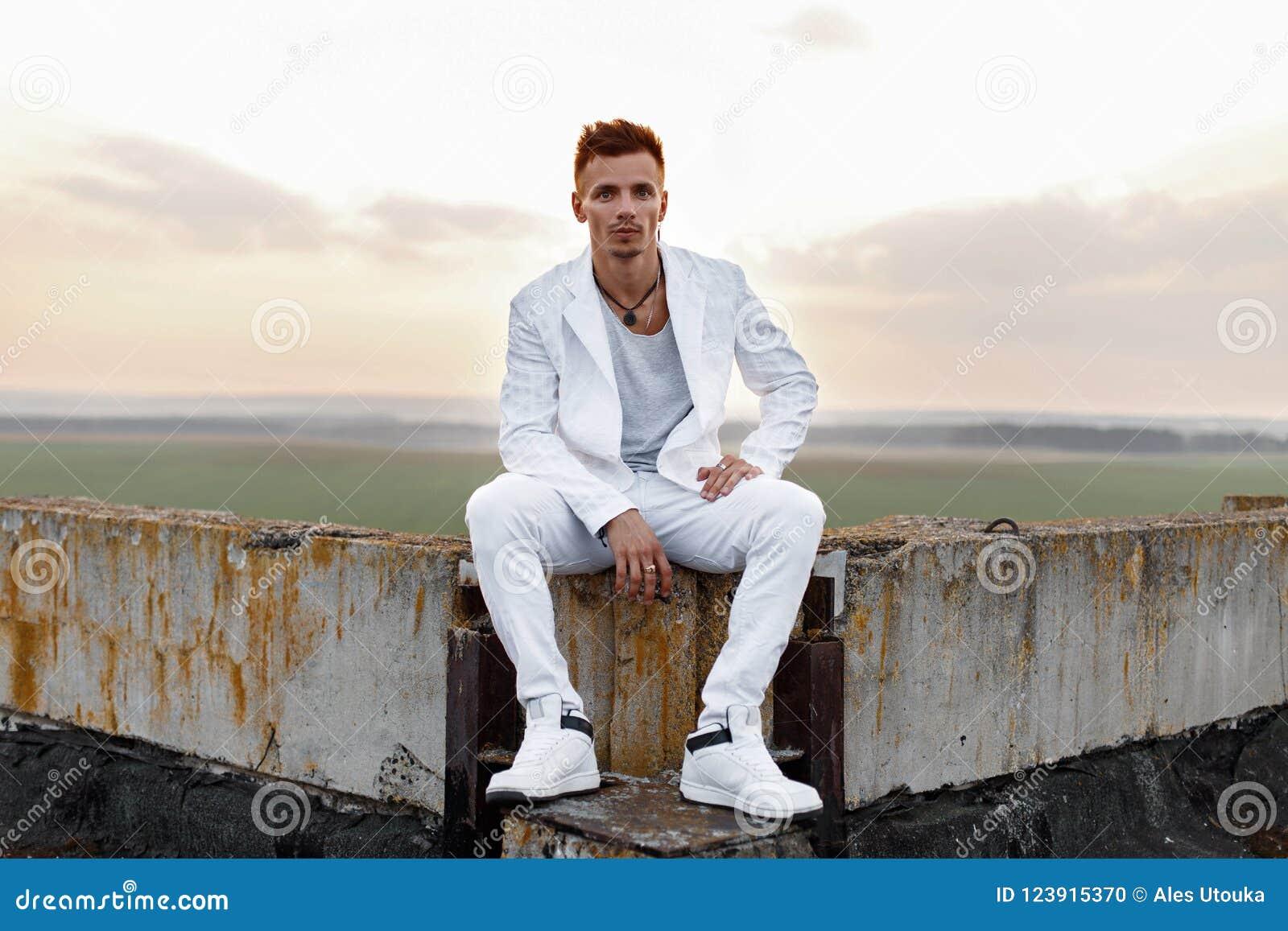 Hombre hermoso joven en la ropa blanca elegante que se sienta en el tejado 9690249ef92