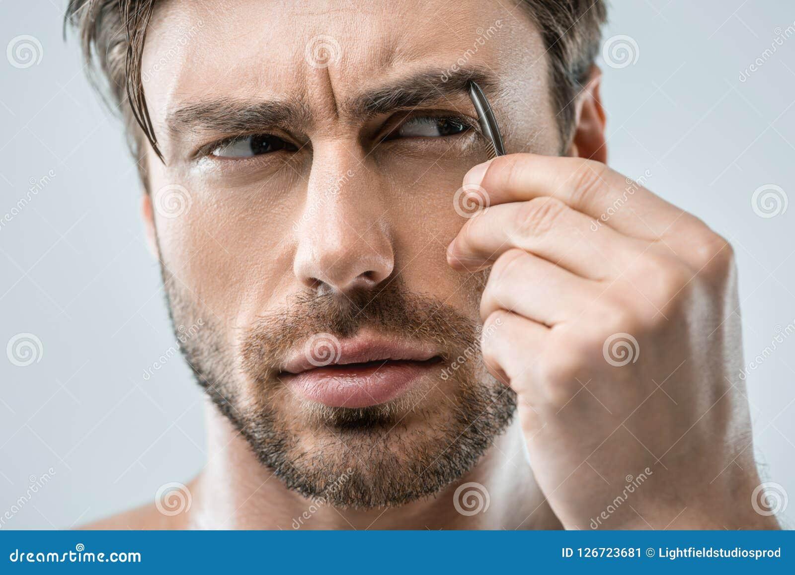 Cejas De Hombre hombre hermoso que despluma las cejas con las pinzas imagen
