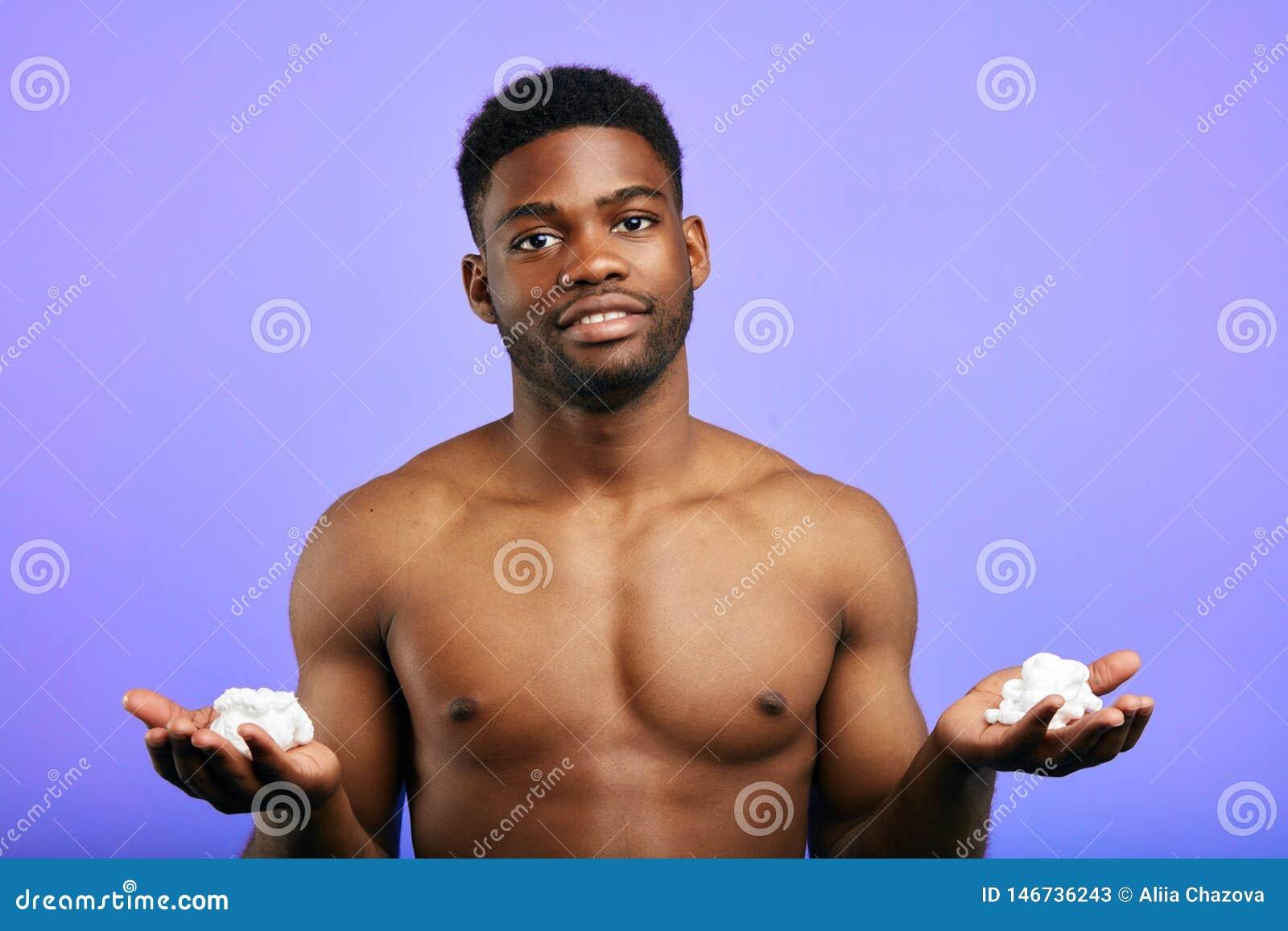 Hombre hermoso que lleva a cabo afeitar la espuma, preparándose para el afeitado, aislado en el fondo azul