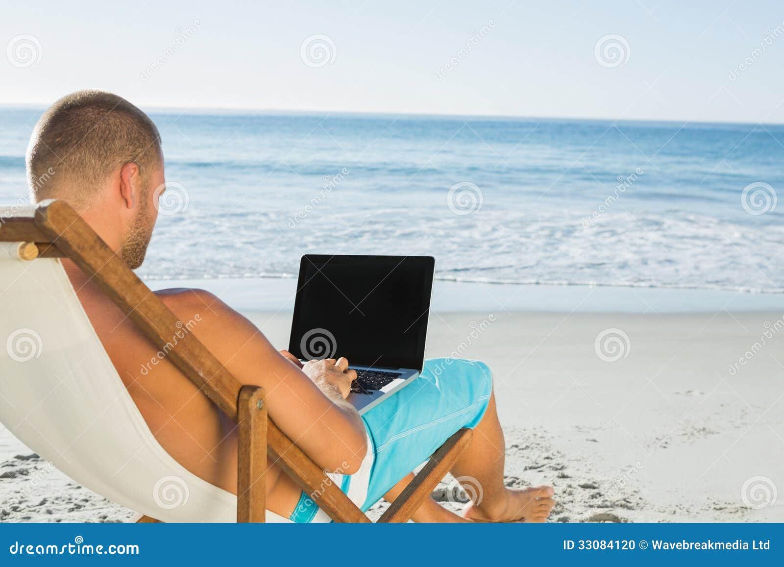Hombre hermoso que mecanografía en su ordenador portátil mientras que se sienta en su cubierta chai