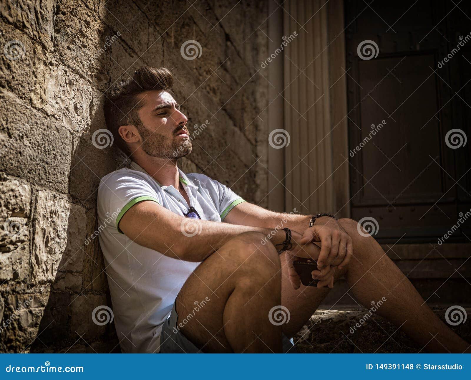 Hombre hermoso que se sienta en la ciudad de la playa