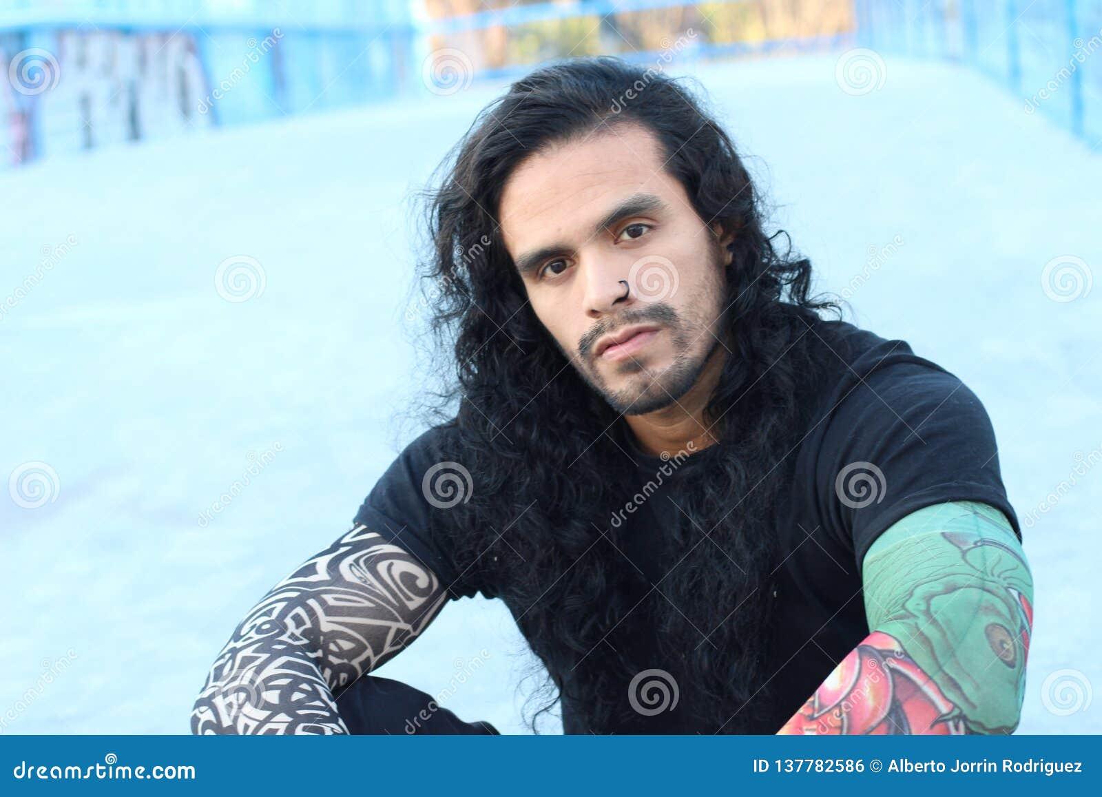 Hombre hispánico de mirada duro con el pelo y los tatuajes largos