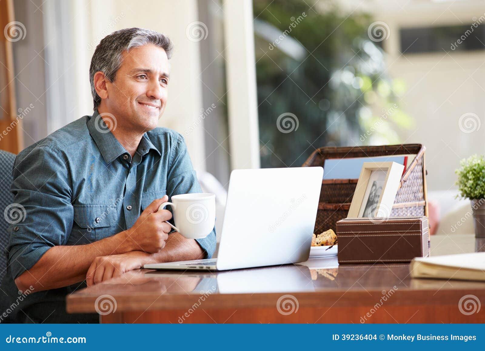 Hombre hispánico maduro que usa el ordenador portátil en el escritorio en casa