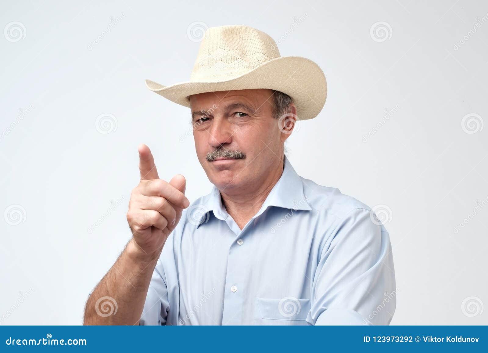 Hombre hispánico maduro serio en el sombrero de vaquero que muestra los dedos índices para arriba, dando consejo o la recomendaci